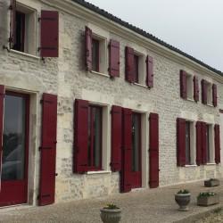 Façade de maison charentaise avec fenêtre rouge en aluminium