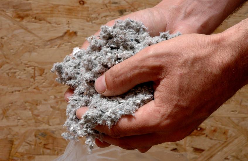 ouate cellulose pris à pleine main par un ouvrier sur un chantier d'Angoulême