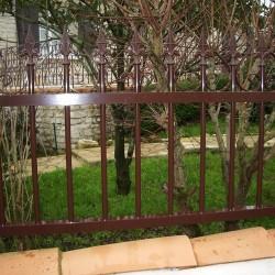 Clôture aluminium rouge sombre donnant sur un jardin de maison à Pisany