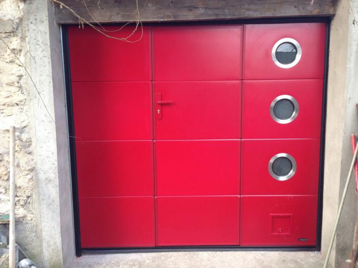 porte de garage battante avec 3 petite fenêtre de style oeil de boeuf